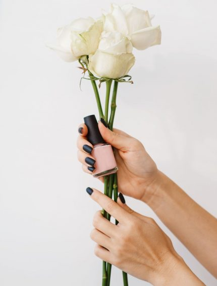 woman-holds-nail-varnish-and-flowers-beauty-salon-U2366SW.jpg